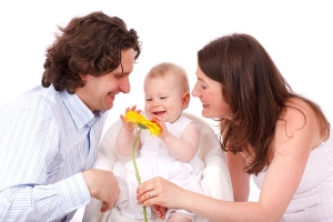 Mother, father and child playing with flower